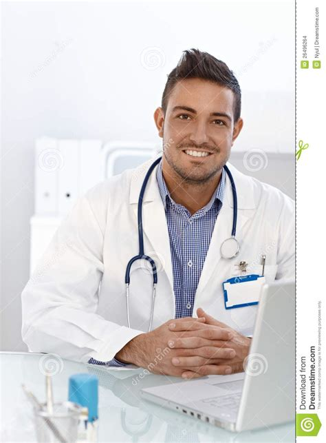 Happy Doctor Sitting At Desk Stock Images - Image: 26496264